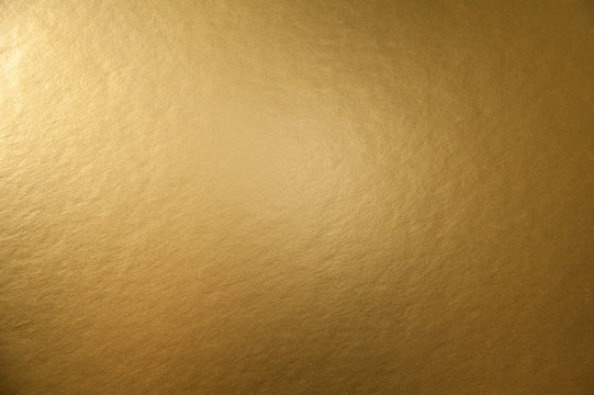 Texture of golden metallic paper background for design Christmas or New Year's party cards