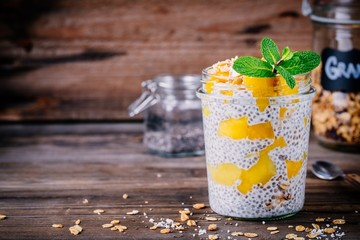 healthy vegan breakfast, chia pudding with mango and granola in the jar on wooden background