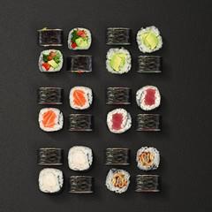 Japanese cuisine. Sushi rolls set over dark background.