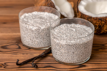 chia pudding in two glass, decorated  vanilla pods and coconuts on wooden background, healthy detox lifestyle concept
