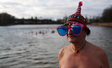 Members of the Berliner Seehunde (Berlin Seals) ice swimmers club take a dip in lake Orankesee during their traditional New Year's swimming event in Berlin