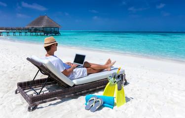 Arbeiten im Urlaub: Mann mit Laptop auf Liege am tropischen Strand