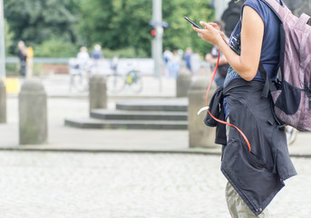Young tourist girl using mobile smartphone searching location while travelling, on vacations. Smartphone is connected by red cable with powerbank in pocket of her jacket.