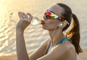Running woman in sport sunglasses drink. Female runner with her