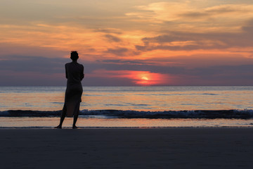 beautiful woman Standing alone Watching the sunset on the beach. Evening time Silhouette style