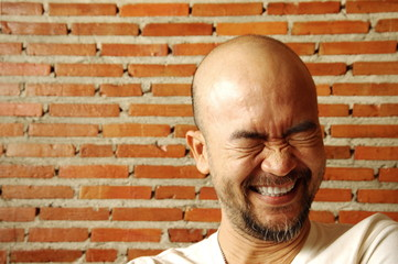 portrait Asian Japanese beard bald laughing man with brick wall background