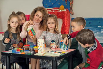 children draw at the table with the teacher