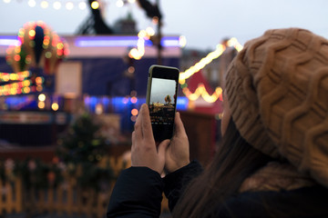 the girl at the Christmas market takes a picture of the carousel on the phone