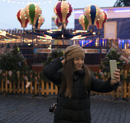 young woman at the Christmas market doing selfie on the phone