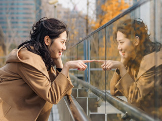 Beautiful Chinese girl looking at her mirror image in glass. Wall mural