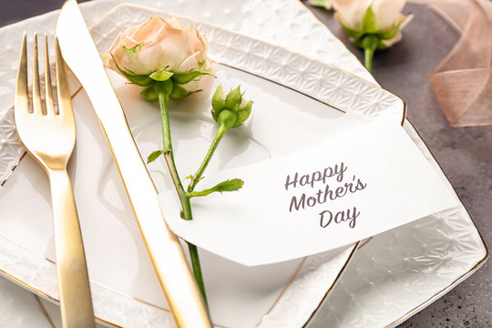Elegant table layout for dinner with flowers and greeting card