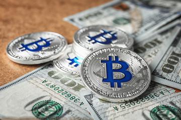 Silver bitcoins and dollar bills on table, closeup