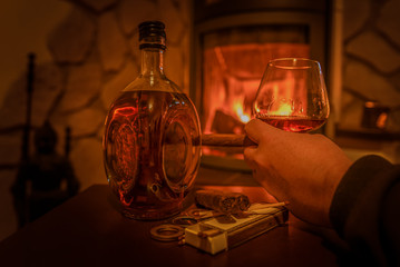 Time to enjoy! A man is holding in his hand a glass of cognac and a cigar. On the table is a konjac bottle and matches and a cigar cutter. In the background a fireplace. Focus on the hand with the gla