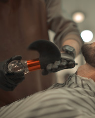 Man's hands in gloves doing a haircut for man with dark hair and beard at barber shop, close up portrait, copy space.
