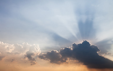 The evening sky is have a beam of light passing through the layers of clouds caused by sun