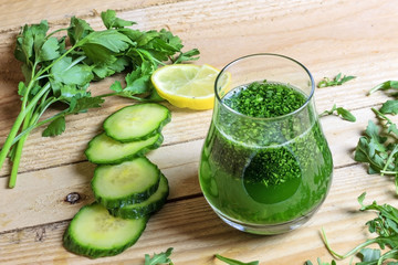 Healthy green juice with parsley and cucumber on wooden background