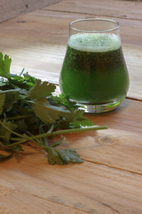 Healthy green juice with parsley on wooden background