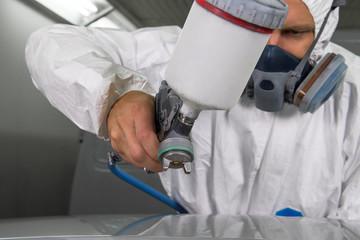 Painter spray gun in the hands of a painter.