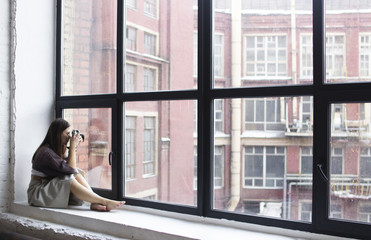 a young woman sits on a windowsill with large windows and takes pictures