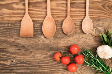 Tavola con mestoli, rosmaino e pomodori
