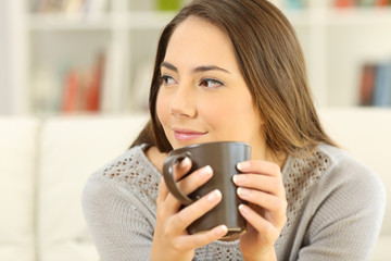 Pensive woman holding a coffee mug looking at side