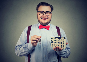 Smiling man with toy house and keys
