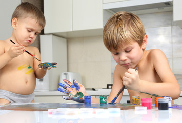 two little boy paint on a white table