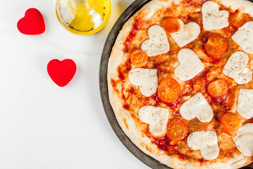 Valentine holiday food concept, pizza margarita with heart shaped cheese, white marble background, copy space top view