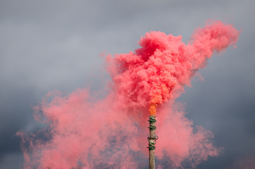 Colorful smoke bombs against a cloudy sky
