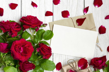 blank greeting card and envelope with red roses flowers, petals and gift box