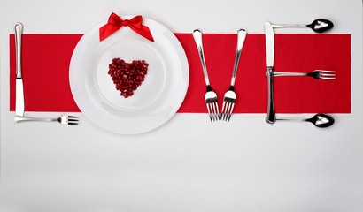 Love word from the spoons knives and forks and white plate with Pomegranate seed in shape heart on white background on red napkin line background.Valentine's day creative background.Concept love