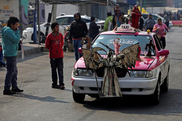 A figure of Santa Muerte or The Saint of Death is seen on a taxi during the first prayer of the New Year at Tepito neighborhood in Mexico City