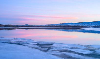 Purple Sunset - Purple sunset clouds over a melting icy mountain lake.
