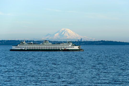 Edmonds–Kingston Ferry - A ferry is on its route crossing Puget Sound between Edmonds and Kingston, with Mount Rainier and Seattle Downtown shining in the evening sunlight in the background.