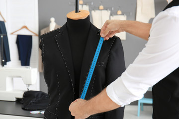 Tailor taking measurements of mannequin in atelier