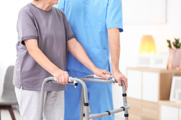 Senior woman walking with assistance of young caregiver indoors