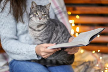 Young woman with cat relaxing while reading book at home on winter day