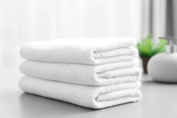 Stack of white clean towels on table in bathroom