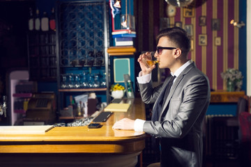 Young handsome man sitting at bar counter and drinking