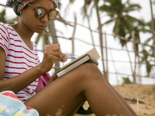 Girl draws watercolor on the beach