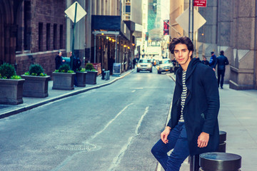 City life. Young handsome man wearing fashionable trench coat with hood, sitting on metal pillar on narrow vintage street in New York, waiting, relaxing. Cars, people on background. Filtered effect