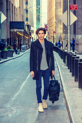 City life. Traveling in New York. Young handsome man wearing black fashionable trench coat with hood, blue jeans, boots, carrying hand bag, walking on narrow vintage street. Filtered effect
