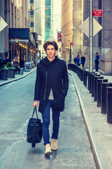 City life. Young handsome man wearing black fashionable trench coat with hood, blue jeans, boots, carrying hand bag, walking on narrow vintage street in New York. Filtered effect