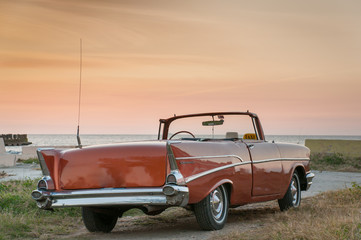 Classic convertible car at sunset on the coast of Havana. Cuba