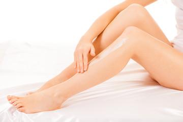 woman apply skin cream on legs