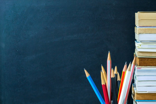 Pencils and books with chalkboard background. Education concept.