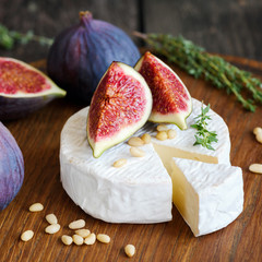 Camembert cheese with figs and pine nuts on wooden cutting board. Close up view, square composition
