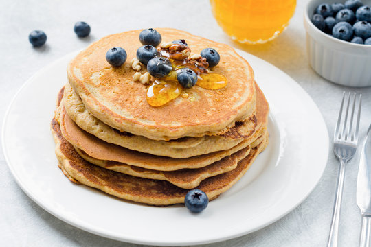Closeup view of pancakes stack with blueberries, walnuts and honey on white plate. Tasty healthy breakfast food. Horizontal