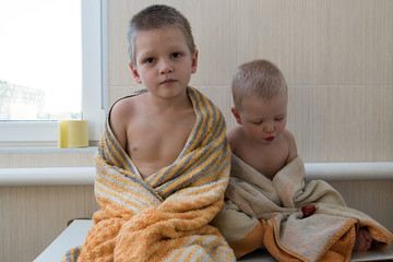 Happy boys are toweled. The child plays with foam and soap bubbles in a sunny bathroom with a window. A little bathing baby. Water activities for children. Hygiene and skin care for children