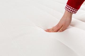 Woman's hand pressing a mattress